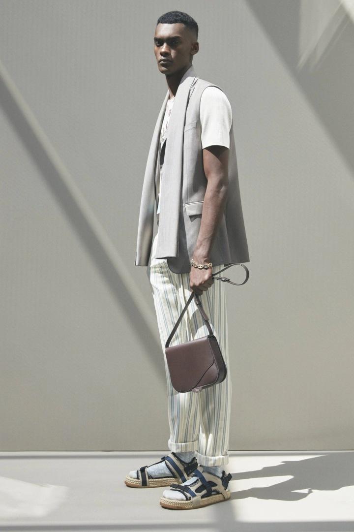 Muž v pruhovaných kalhotách a šedé vestě Dior