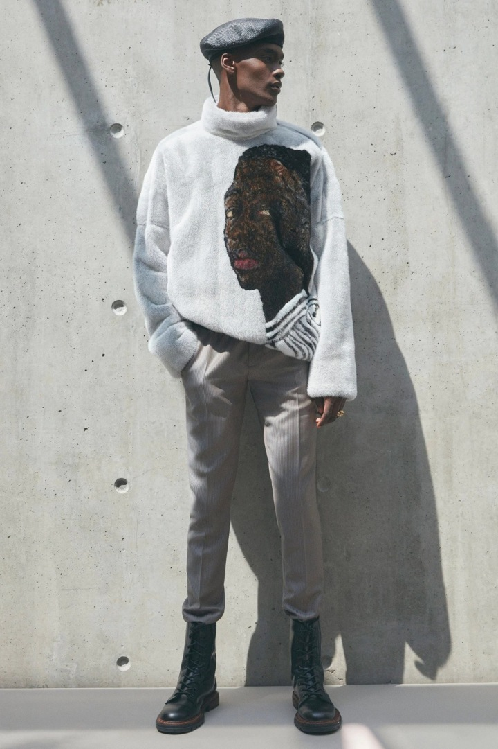 Muž v béžových kalhotách a bílém svetru Dior