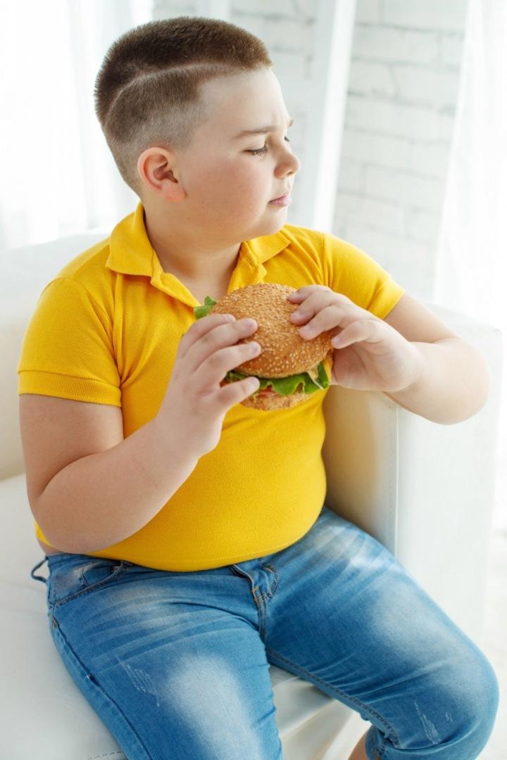 Dítě jí hamburger.