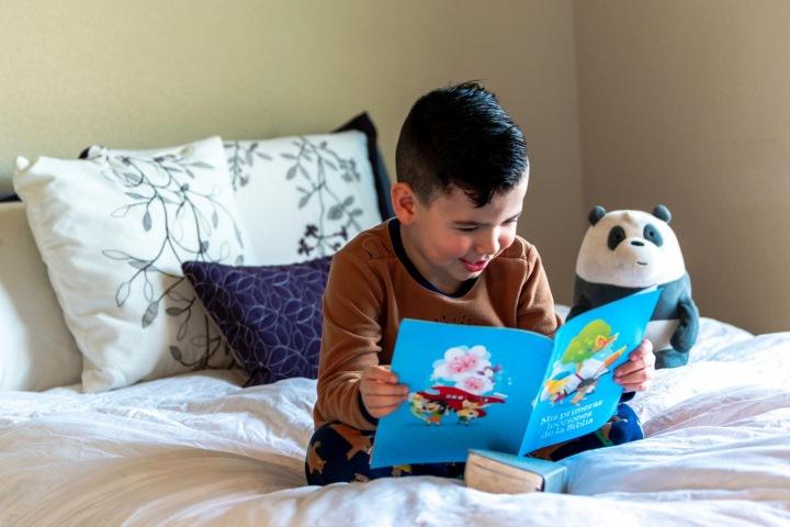 Dítě s knihou v posteli