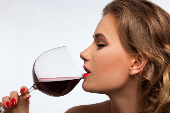 Žena pije víno.