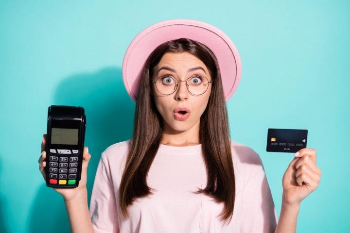 Překvapená dívka v růžovém kloboučku s kreditní kartou v ruce