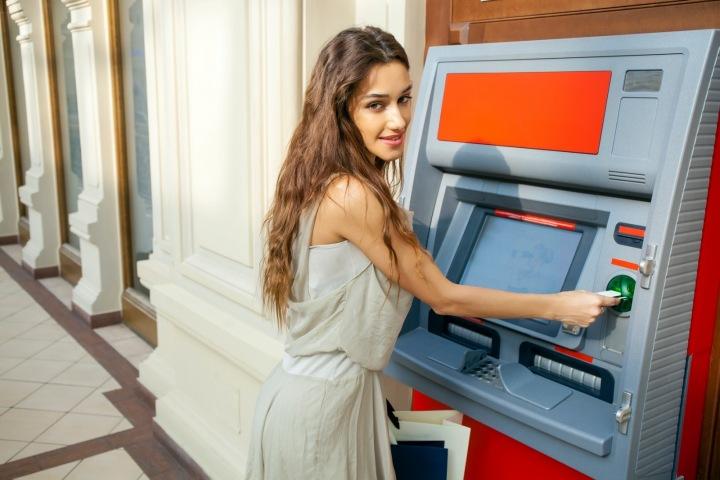Dívka v letních šatech vybírá z bankomatu