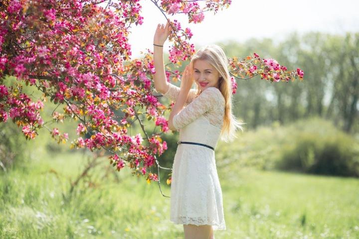 Žena pod rozkvetlým stromem.