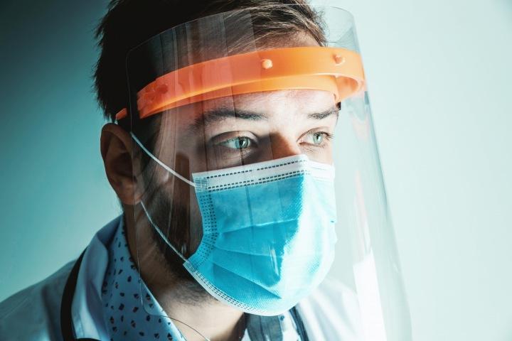 Muž s lékařskou rouškou a ochranným štítem
