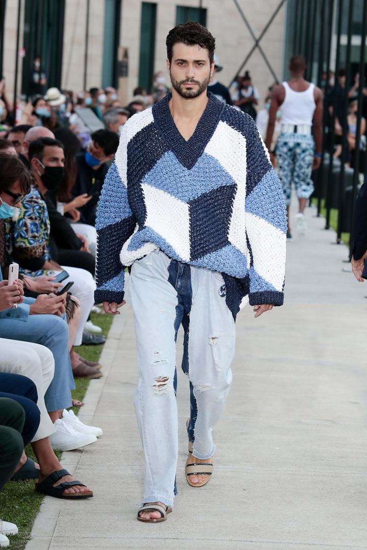 Muž v modrém svetru a džínách Dolce & Gabbana