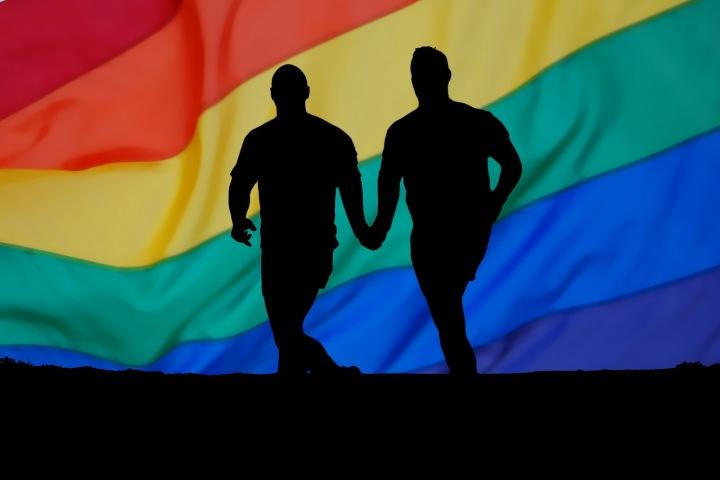 Dvě mužské postavy se drží za ruce na podkladu duhové vlajky.