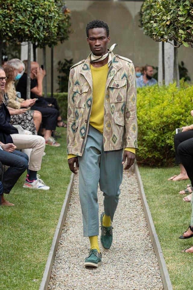 Muž v šedých kalhotách a žlutém svetru Etro
