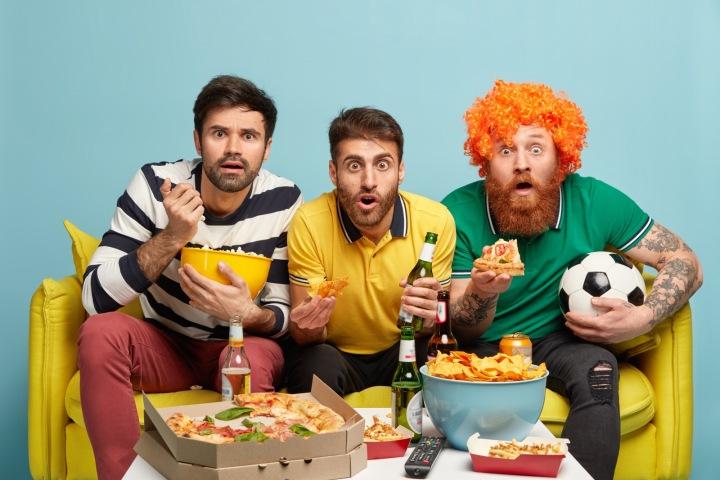 Fotbalové fandění má mnoho podob. Trojice fotbalových fanoušků s pivem a pizzou.