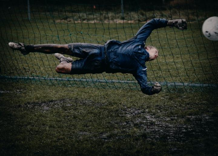 Fotbalový brankář se snaží chytit míč
