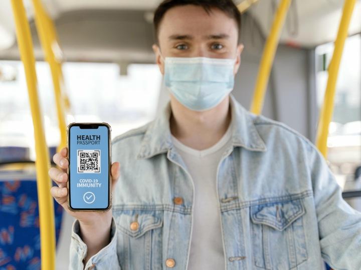 Mug držící telefon s virtuálním zdravotním pasem