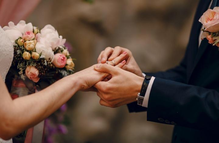 Ruce novomanželů měnících si snubní prsteny