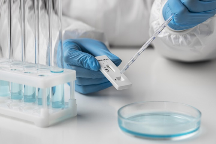 Pracovník laboratoře zpracovává test na koronavirus