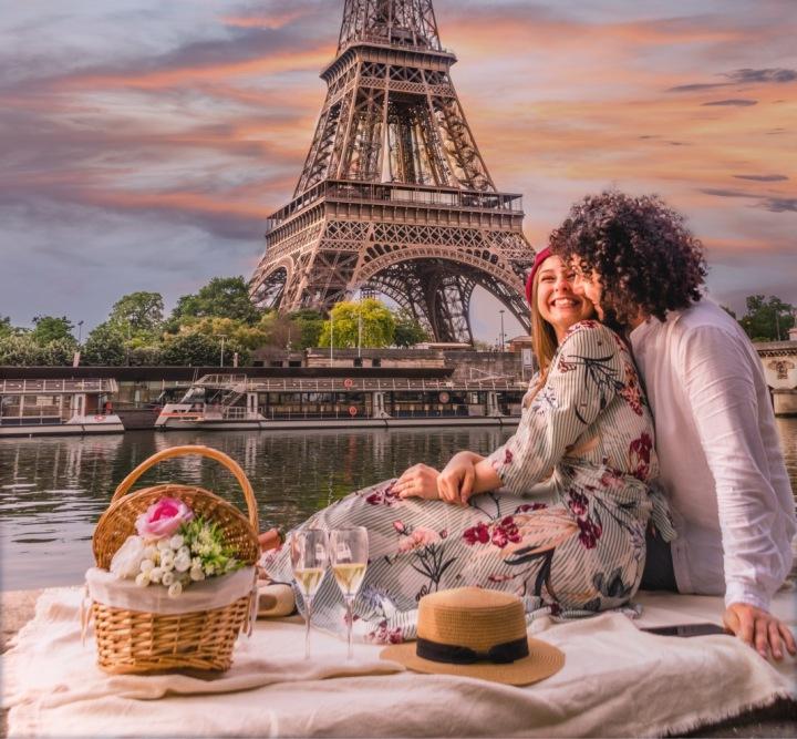 Pár užívající si piknik s výhledem na Eiffelovku