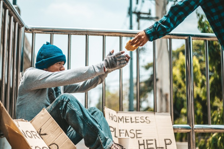 Pán sedí na ulici a bere si jídlo od kolemjdoucího.