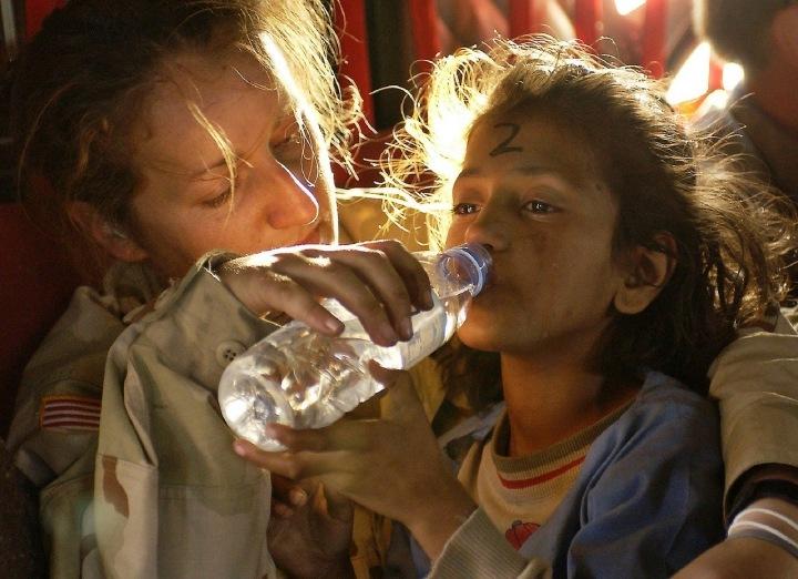 Děvče pije v uprchlickém táboře vodu