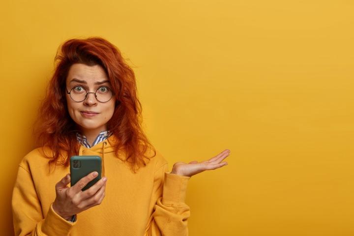 Zmatená a tápající mladá žena s telefonem.