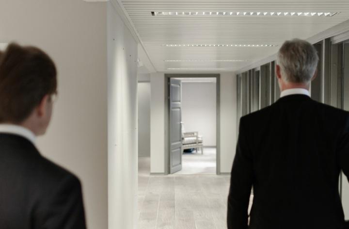 Dva muži zezadu kráčejí kancelářskou chodbou