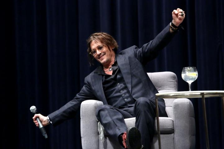 Johnny Depp na diskusi v elegantním obleku a pohorkách.