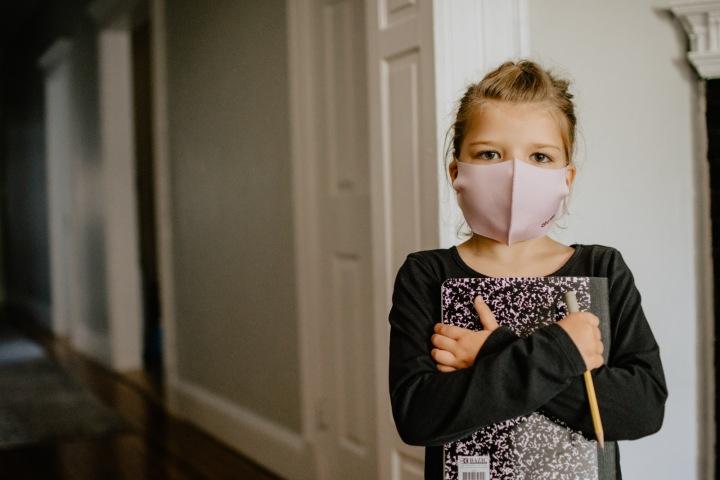 Dívka ve škole s rouškou na ústech