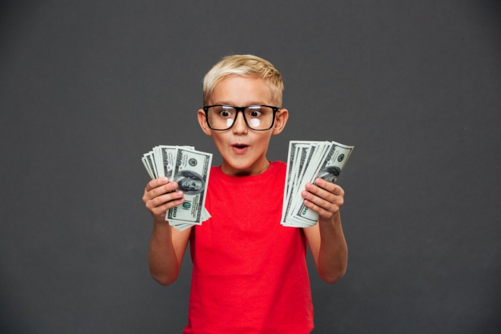 Kluk drží v ruce bankovky.