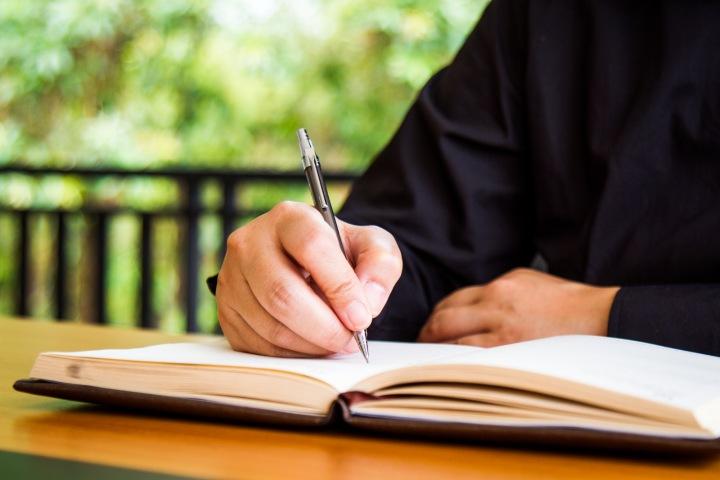 Muž zapisuje do deníku.