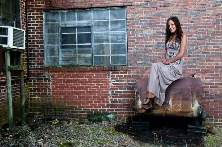 Dívka sedící před cihlovou zdí opuštěného industriálního objektu