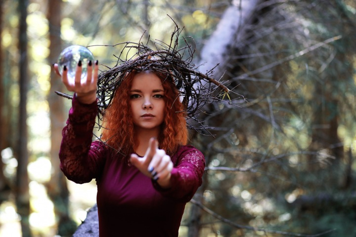 Krásná dívka, věštkyně s křišťálovou koulí v ruce se dívá směle do budoucnosti