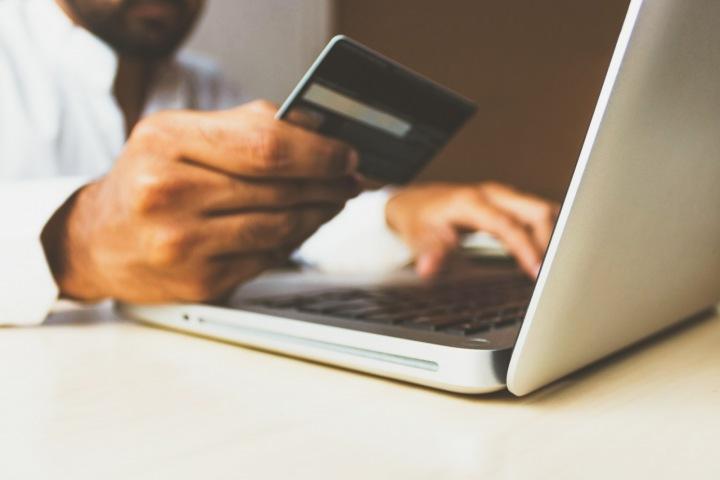 Muž u notebooku s platební kartou