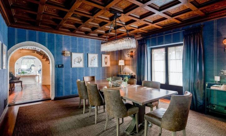 Stylová jídelna s dominantním jídelním stolem a dřevěným kazetovým stropem