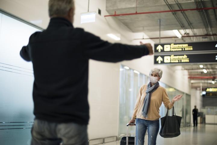 Žena vítá manžela na letišti.