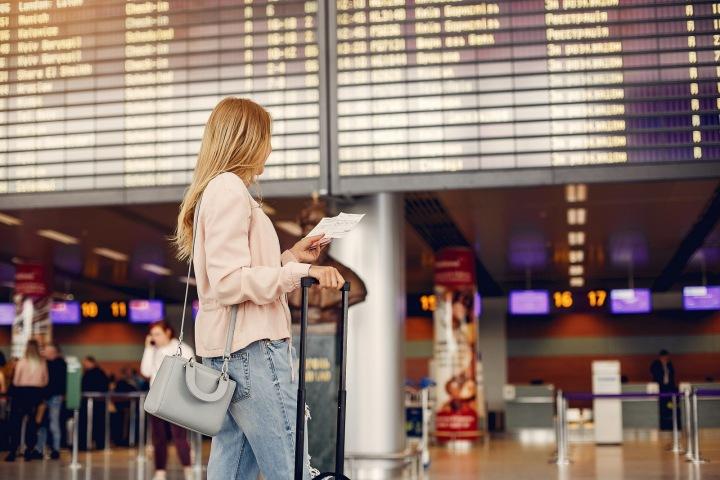 Žena stojí s kufrem na letišti.