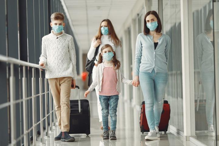 Lidé na letišti s rouškami