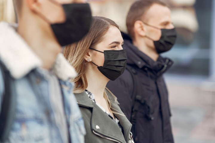 Lidé na ulici postávají v černých rouškách