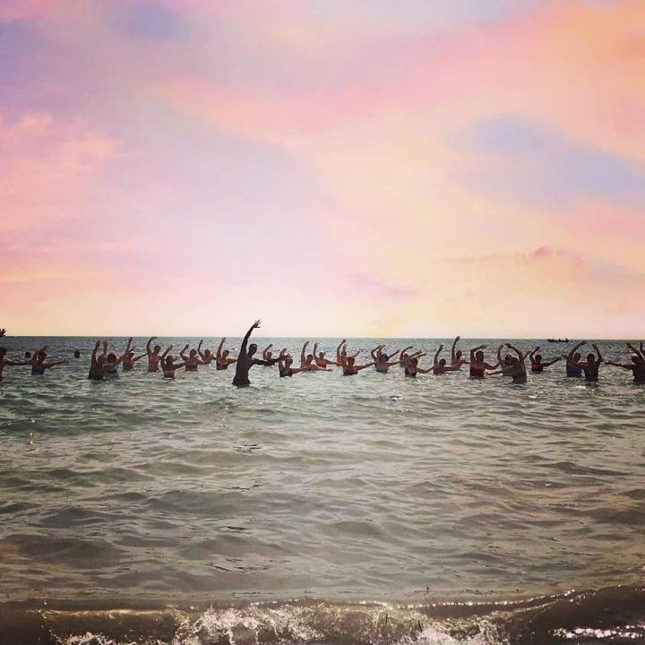 Lidé cvičí jógu v moři.
