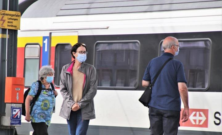 Lidé v rouškách na nádraží.