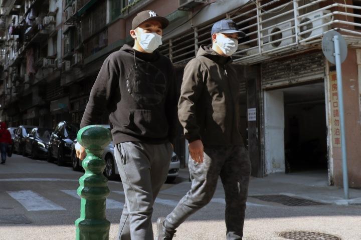 Lidé v rouškách na ulici v Macau
