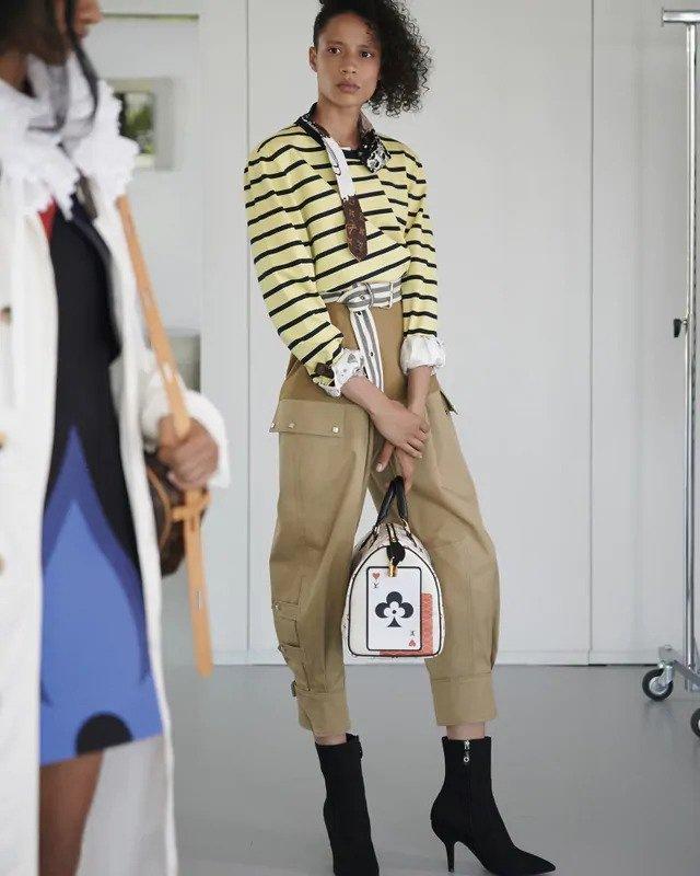 Žena v pruhovaném topu a béžových kalhotách Louis Vuitton