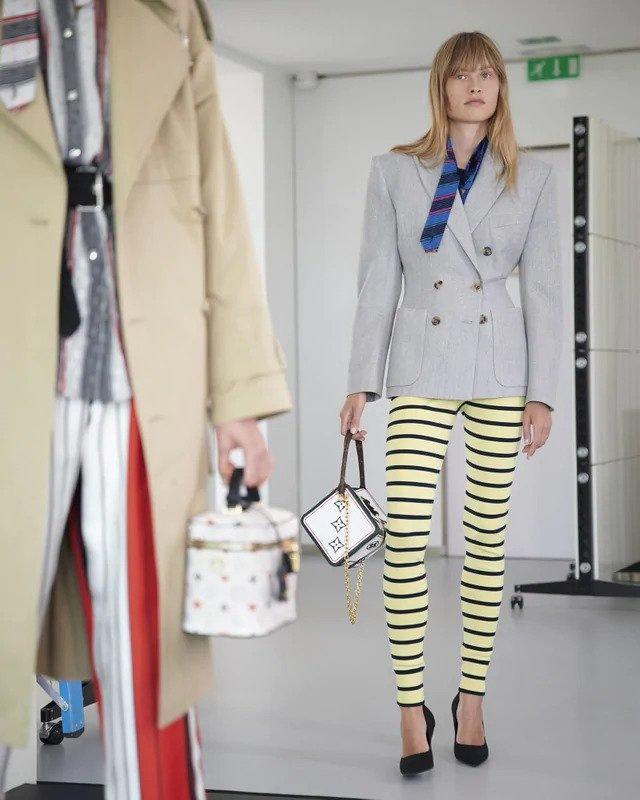 Žena v šedém saku a pruhovaných kalhotách Louis Vuitton