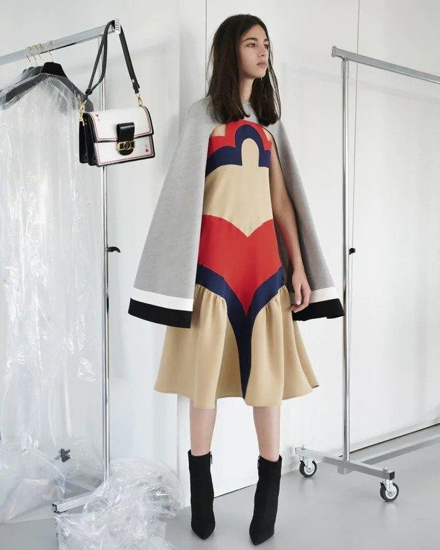 Žena v béžových šatech a šedé peleríně Louis Vuitton