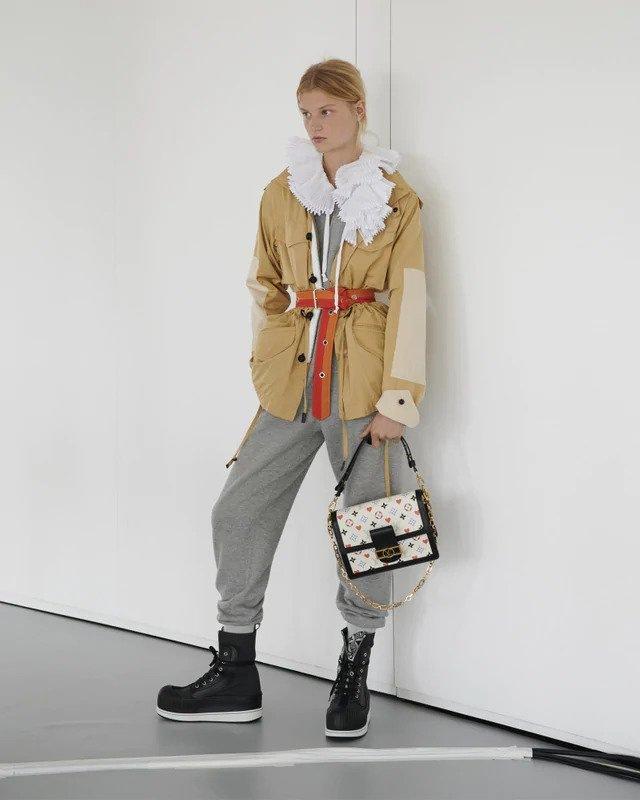 Žena v béžové bundě a šedých teplácích Louis Vuitton