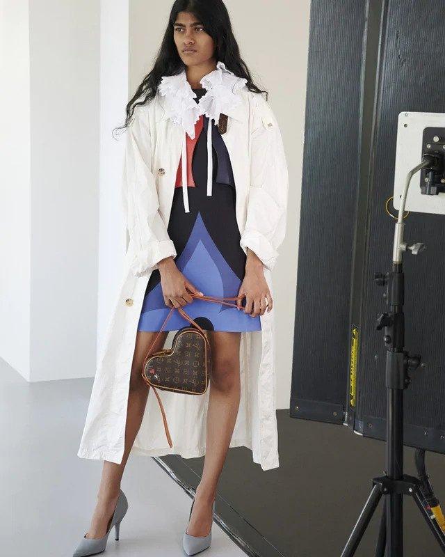 Žena ve fialových mini šatech a bílém trenčkotu Louis Vuitton
