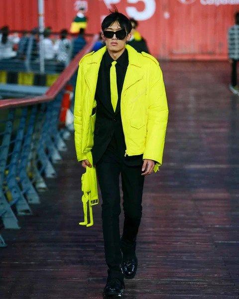 Muž v černém obleku a žluté bundě Louis Vuitton SS 2021
