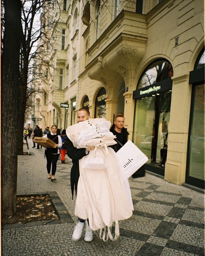 Lukáš Macháček v ulici s oblečením.