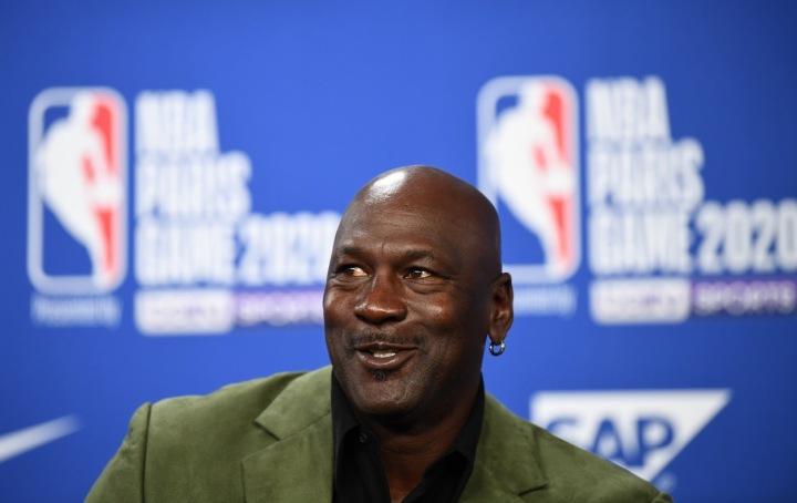 Michael Jordan sedí v zeleném saku, za ním je modré pozadí