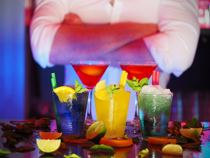 Míchané drinky a barman v pozadí.