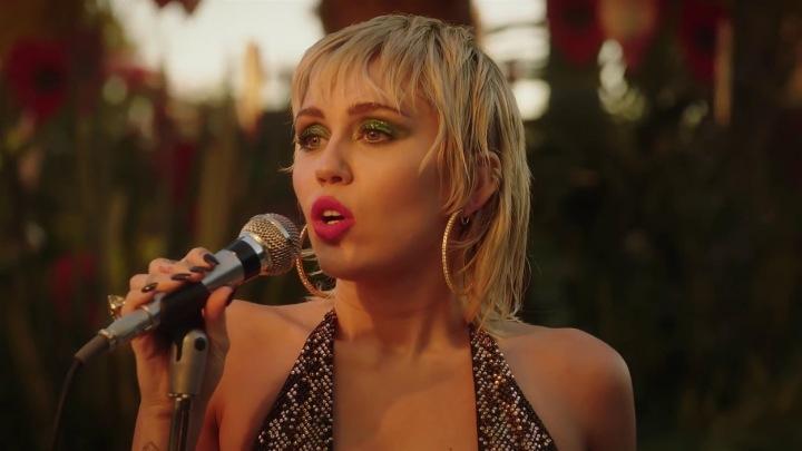 Miley Cyrus zpívá do mikrofonu.