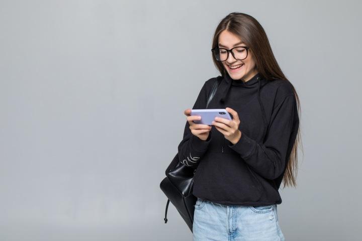 Mladá dívka si hraje na telefonu