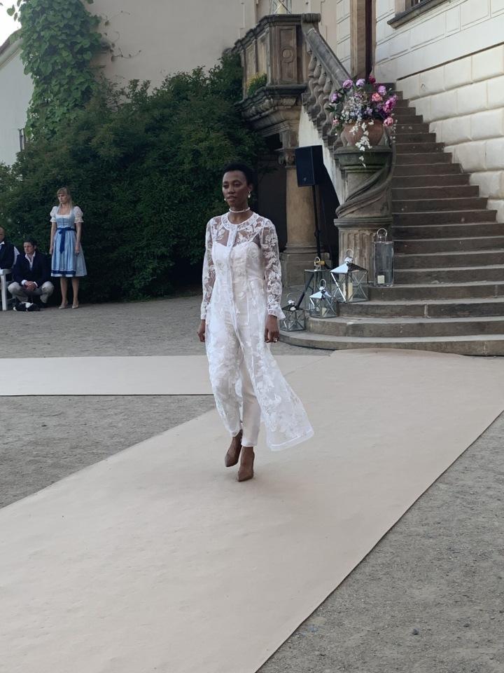 Modelka v bílých kalhotových šatech.
