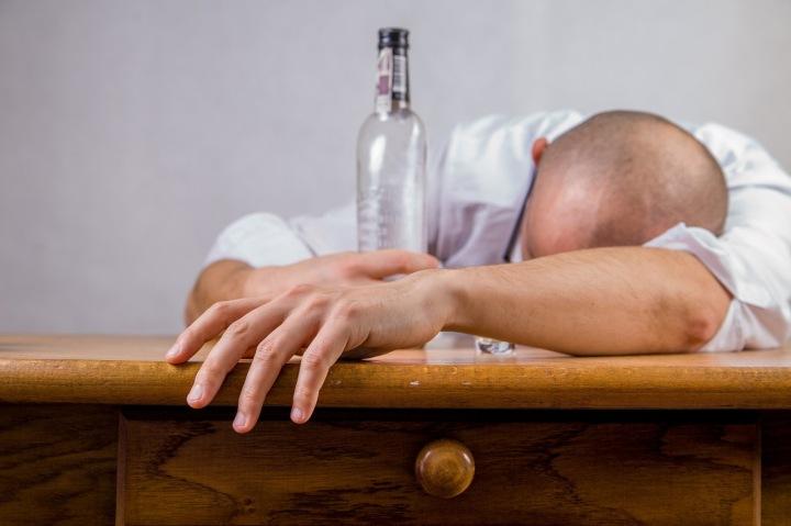 Muž a lahev alkoholu.